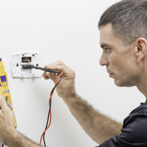 A Technician Checks a Thermostat.