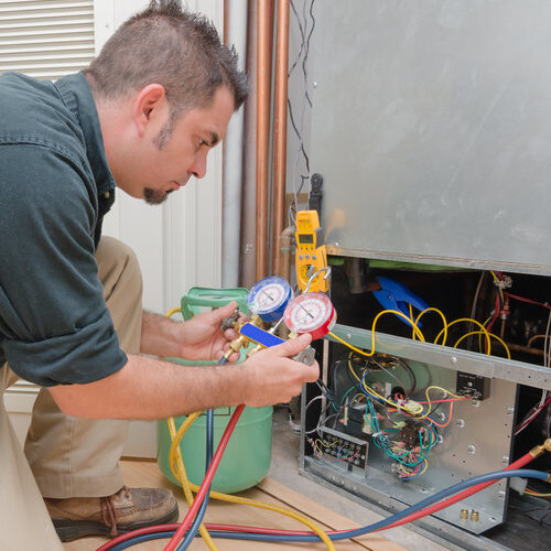 Technician performing a refrigerant recharge.
