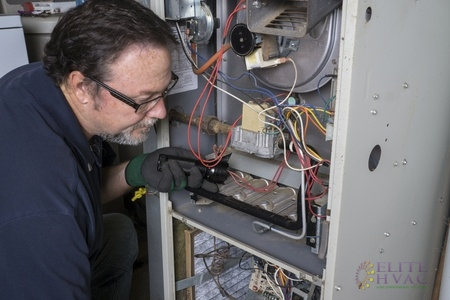 Technician Performing Home Heater Maintenance